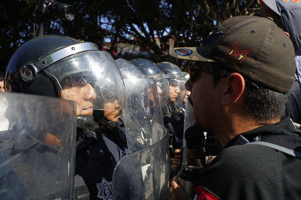 La policía protege un albergue de migrantes centroamericanos de manifestantes que protestan por su presencia, en Tijuana, México, el domingo 18 de noviembre de 2018. (AP Foto/Ramón Espinosa)