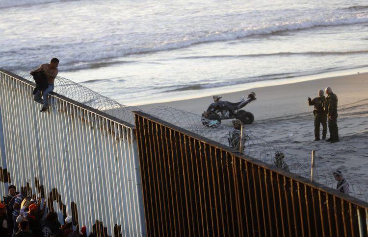 Un migrante centroamericano está sentado sobre la estructura fronteriza que separa México (izquierda) de Estados Unidos (derecha), mientras agentes fronterizos estadounidenses vigilan la escena, el 14 de noviembre de 2018, en esta imagen tomada desde Tijuana, México. (AP Foto/Gregory Bull)
