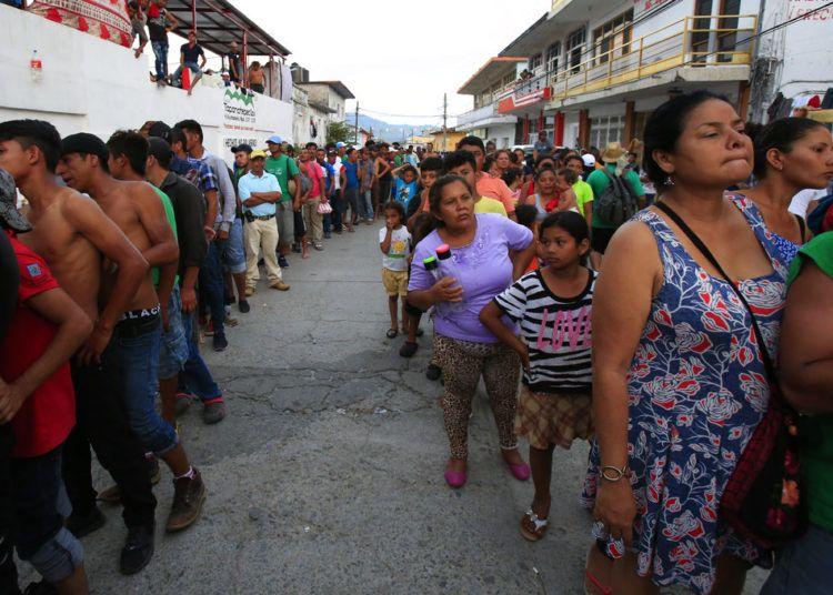Migrantes hacen fila para recibir alimentos donados, parte de una caravana de centroamericanos que intentan llegar a Estados Unidos, en Tapanatepec, México, el domingo 28 de octubre de 2018. (AP Foto/Rebecca Blackwell)