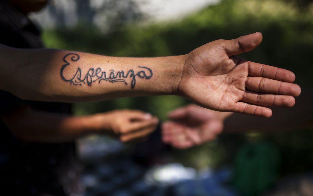 El migrante hondureño Gerson Noel Rivas muestra el tatuaje hecho por el migrante José Manuel de Jesús Sandoval, en un campamento montado por la caravana de miles de centroamericanos en Juchitán, México. Esperanza es el nombre de la madre de Rivas. Foto: Rodrigo Abd / AP.