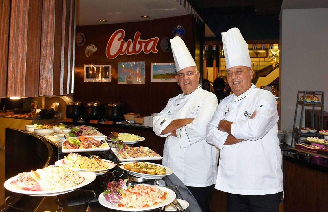 Los chefs cubanos Eddy Fernández (derecha), Presidente de la Federación de Asociaciones Culinarias de Cuba, y Carlos Silvio Otero, con una muestra de creaciones culinarias de la Isla. Foto: @libiamiranda / Twitter.