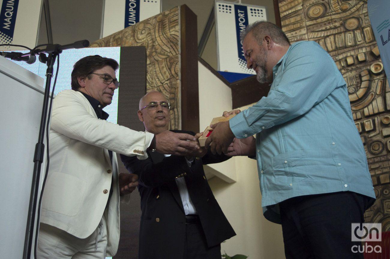 Tom McAlpin (izq) entrega al ministro cubano de Turismo, Manuel Marrero (der) la insignia de Virgin Voyages. Detrás, el periodista Reinaldo Taladrid, maestro de ceremonias del acto realizado en Fihav 2018. Foto: Otmaro Rodríguez.
