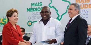 """La expresidenta Dilma Rousseff junto a un médico cubano y al Ministro de Salud de su gobierno, Alexandre Padilha, durante la oficialización legal del programa """"Más Médicos"""" en 2013. Foto: Roberto Stuckert Filho/ PR / Archivo."""