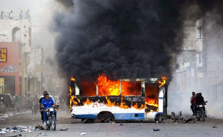 Dos motocicletas pasan junto a un autobús en llamas, incendiado por manifestantes de oposición que exigen saber el destino de los fondos de Petrocaribe, en Puerto Príncipe, Haití, el domingo 18 de noviembre de 2018. (AP Foto/Dieu Nalio Chery)