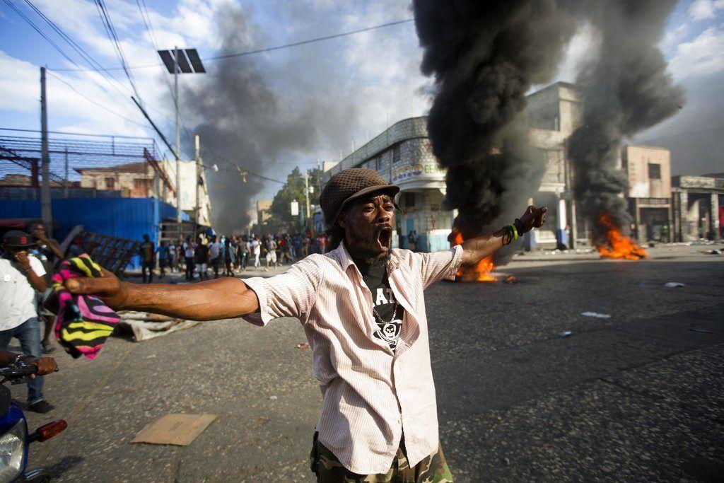 Un manifestante corea consignas contra el gobierno durante una protesta para exigir saber el uso que las autoridades le dieron a los fondos de Petrocaribe, en Puerto Príncipe, Haití, el domingo 18 de noviembre de 2018. (AP Foto/Dieu Nalio Chery)