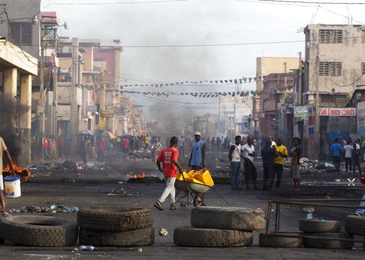 Residentes caminan entre las calles bloqueadas por manifestantes en contra del gobierno en el Boulevard Jean-Jacques Dessalines, una de las principales avenidas comerciales, durante una huelga anti gubernamental el miércoles 21 de noviembre de 2018 en Puerto Príncipe, Haití. Foto: Dieu Nalio Chery / AP.