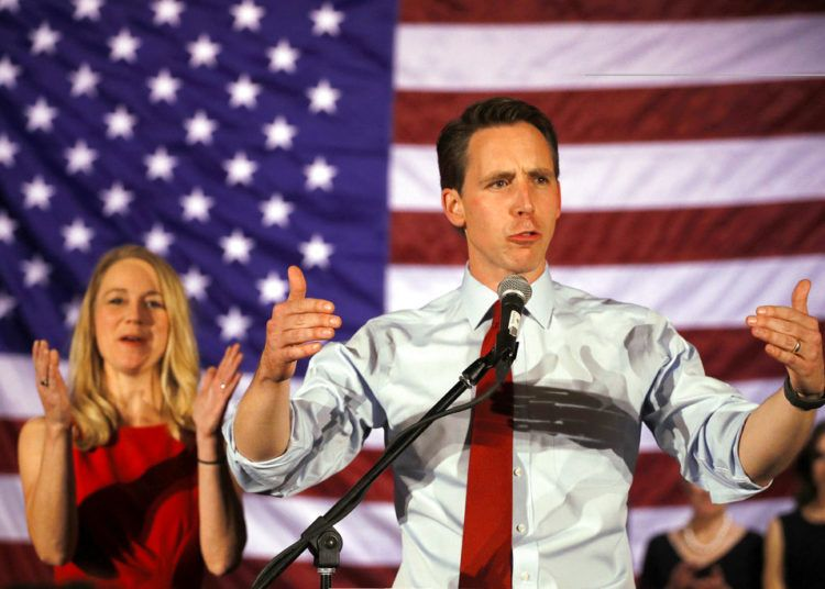 El senador electo Josh Hawley ofrece un discurso tras su victoria en las elecciones de mitad de periodo, mientras su esposa Erin aplaude en el fondo, el 6 de noviembre de 2018 en Springfield, Missouri. (AP Foto/Charlie Riedel)