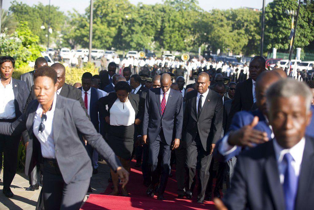 El presidente haitiano Jovenel Moïse, al centro, llega con la primera dama Martine, izquierda, y el primer ministro Jean-Henry Ceant, derecha, a un acto en el 215to aniversario de la batalla de Vertieres, el último paso de los haitianos para obtener su independencia de Francia, en Puerto Príncipe, el domingo 18 de noviembre de 2018. ( AP Foto/Dieu Nalio Chery)