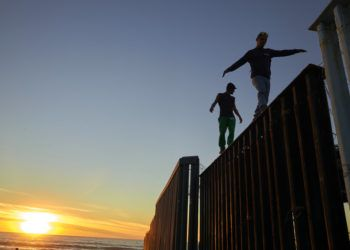En esta imagen, tomada el 14 de noviembre de 2018, dos migrantes centroamericanos caminan sobre el muro que separa México de Estados Unidos, en Tijuana, México. Integrantes de una caravana de migrantes centroamericanos lograron llegar a la frontera estadounidense tras recorrer los últimos kilómetros de su largo viaje en buses y camiones. (AP Foto/Gregory Bull)