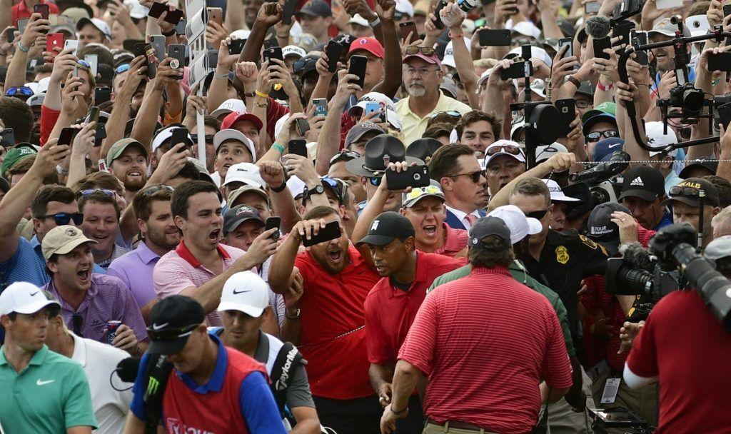 Tiger Woods, en el medio, y Rory McIlroy, abajo al extremo izquierdo, emergen entre el público durante el 18vo hoyo del Campeonato del Tour en Atlanta, el 23 de septiembre de 2018. (AP Foto/John Amis)