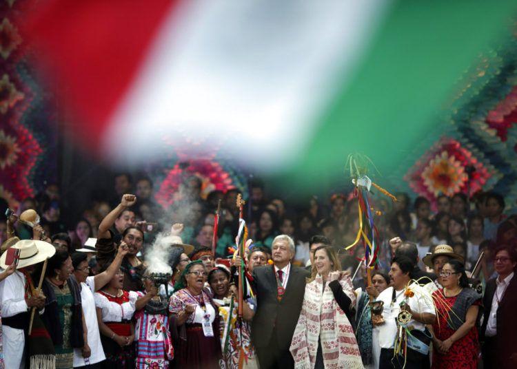 El nuevo presidente mexicano, Andrés Manuel López Obrador, al centro, sostiene un bastón de mando durante una ceremonia tradicional indígena en el Zócalo de la Ciudad de México el sábado 1ro de diciembre de 2018. A la derecha aparece de pie su esposa, Beatriz Gutiérrez Müller. Foto: Eduardo Verdugo / AP.