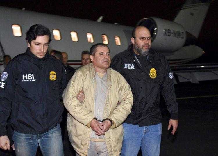 """En esta fotografía del 19 de enero de 2017 dos agentes escoltan a Joaquín """"El Chapo"""" Guzmán de un avión hacia una caravana de camionetas en el Aeropuerto MacArthur de Long Island, en Ronkonkoma, Nueva York. Foto: U.S. Law Enforcement vía AP."""