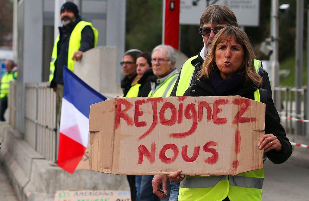 """Una manifestante muestra un cartón con el lema """"Únase"""" (en francés) durante una protesta en una autopista en Biarritz, en el suroeste de Francia, el 5 de diciembre de 2018. Foto: Bob Edme / AP."""