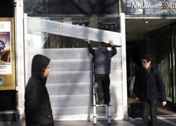 Un hombre protege el escaparate de una tienda en los Campos Elíseos, en París, el 14 de diciembre de 2018. Foto: Francois Mori / AP.