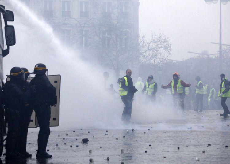 Manifestantes vestidos con chalecos amarillos se enfrentan a los cañones de agua de la policía durante una protesta cerca de la avenida de los Campos Elíseos, en París, el 1 de diciembre de 2018. Foto: Kamil Zihnioglu / AP.