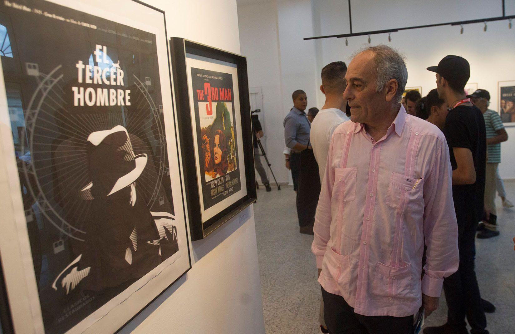 """Alberto Navarro González, embajador de la Unión Europea en Cuba, observa los carteles de la exposición """"Clásicos restaurados del cine europeo"""", en la galería 23 y 12, de La Habana. Foto: Yander Zamora / EFE."""