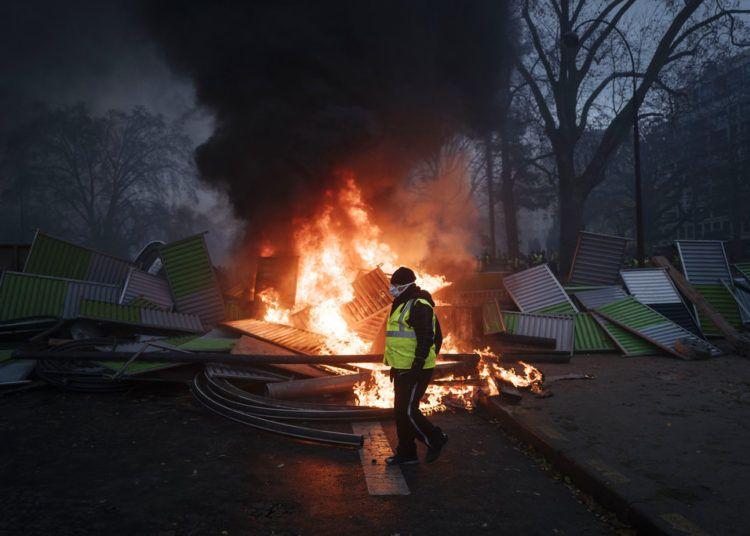 Un manifestante pasa frente a una barricada cerca del Arco del Triunfo en los Campos Elíseos, durante una protesta el sábado 1ro de diciembre de 2018, en París. Foto: Kamil Zihnioglu / AP.