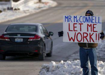 Un trabajador de la Agencia de Protección Ambiental de EEUU (EPA, por sus siglas en inglés) afectado por el cierre parcial del gobierno protesta con un cartel ante las oficinas del senador Mitch McConnell, en Park Hills, Kentucky, el 22 de enero de 2019. Foto: Bryan Woolston / AP.