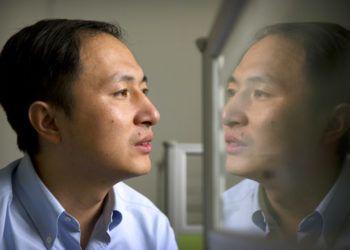 En esta imagen de archivo, tomada el 10 de octubre de 2018, la imagen de He Jiankui se refleja en un panel de cristal mientras trabaja en una computadora en un laboratorio en Shenzhen, en la provincia de Guangdong, en el sur de China. Foto: Mark Schiefelbein / AP.