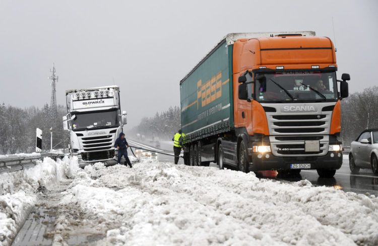 Dos camioneros se ayudan después de haber quedado atrapados por una fuerte nevada en la autopista A8 cerca de Holzkirchen, en el sur de Alemania, el lunes 7 de enero de 2019. Foto: Tobias Hase / dpa vía AP.