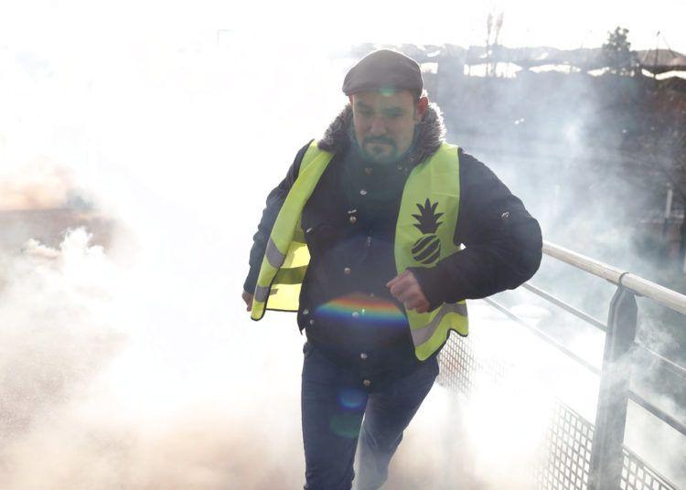 Un manifestante se aleja del gas lacrimógeno rociado por la policía antimotines durante una manifestación de sindicalistas y chalecos amarillos, en Creteil, en las afueras de París, el miércoles 9 de enero de 2019. Foto: Thibault Camus / AP.