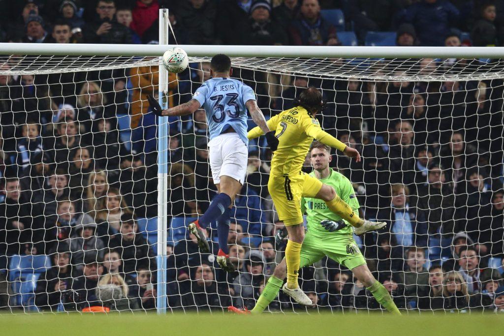 El delantero del Manchester City, el brasileño Gabriel Jesus (33), anota el quinto gol de su equipo ante el defensa del Burton Albion, Johmn Brayford, y el portero Bradley Collins, durante el juego de ida de las semifinales de la Copa de Liga en el estadio Etihad, en Manchester, Inglaterra, el miércoles 9 de enero de 2019. (AP Foto/Dave Thompson)