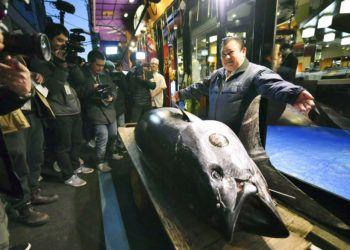 El propietario de Kiyomura Corp. Kiyoshi Kimura, a la derecha, posa junto al atún aleta azul que compró en una subasta durante la subasta de Año Nuevo frente a su restaurante Sushi Zanmai en Tokio, el sábado 5 de enero de 2018. Foto: Koki Sengoku / Kyodo News vía AP.