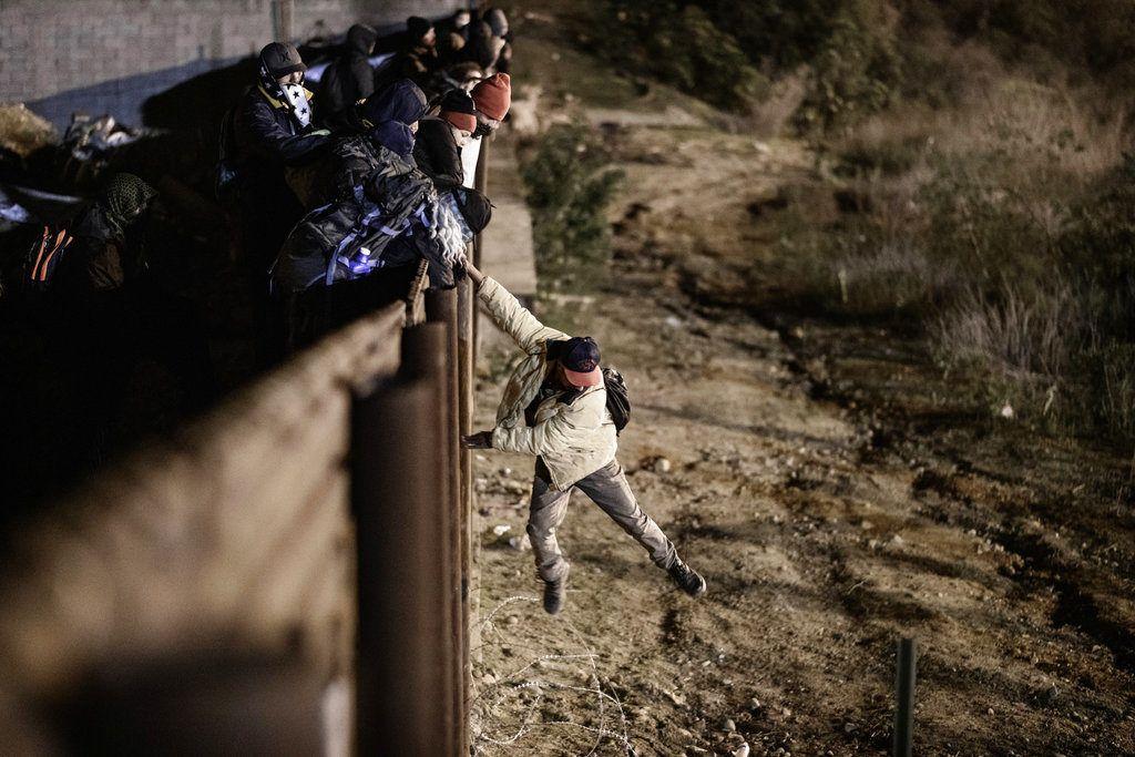 Un migrante salta la valla fronteriza entre Tijuana, México, y San Diego, California, el martes 1 de enero de 2019. Foto: Daniel Ochoa de Olza / AP.