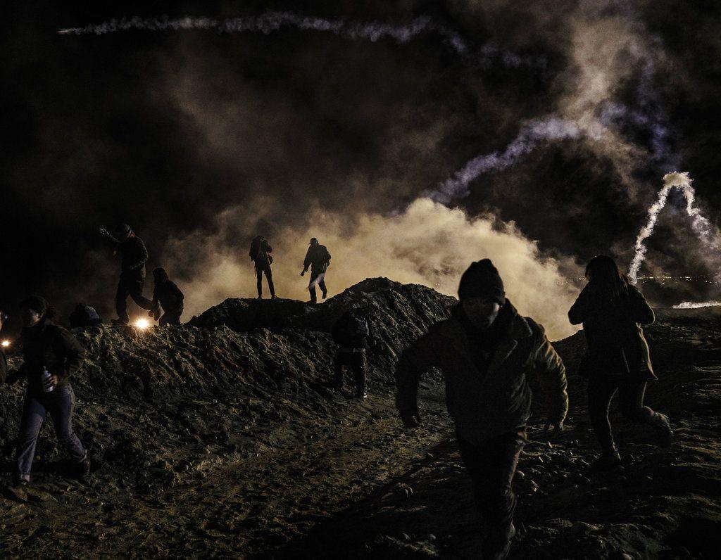 Algunos migrantes corren mientras agentes de protección fronteriza de Estados Unidos lanzan gas lacrimógeno hacia territorio mexicano después que los primeros trataron de saltar la valla fronteriza de Tijuana a San Diego, el martes 1ro de enero de 2019. Foto: Daniel Ochoa de Olza / AP.
