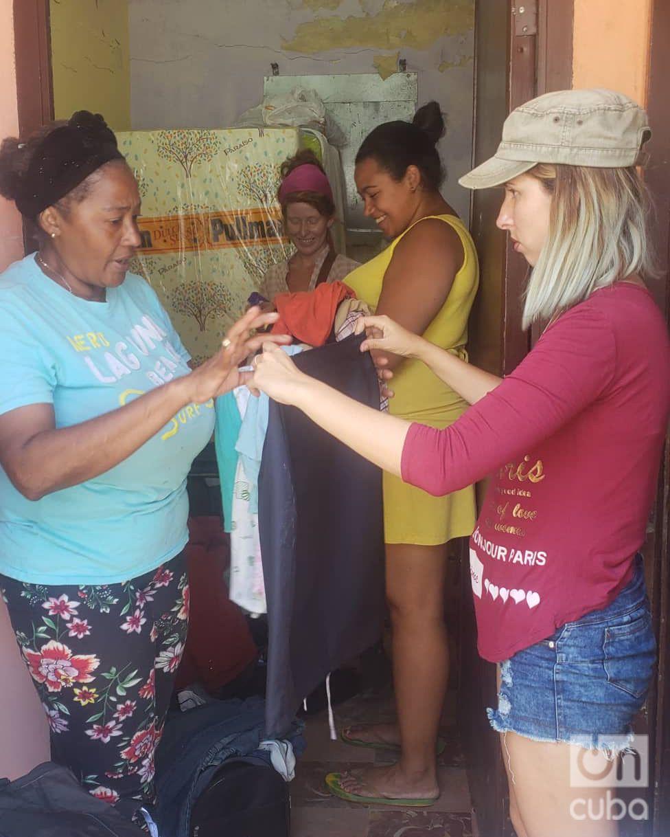 """Mirurgia Stevens (izq) y su familia recibe una donación de los jóvenes del grupo """"Ayuda Solidaria"""". Foto: Michel Hernández."""