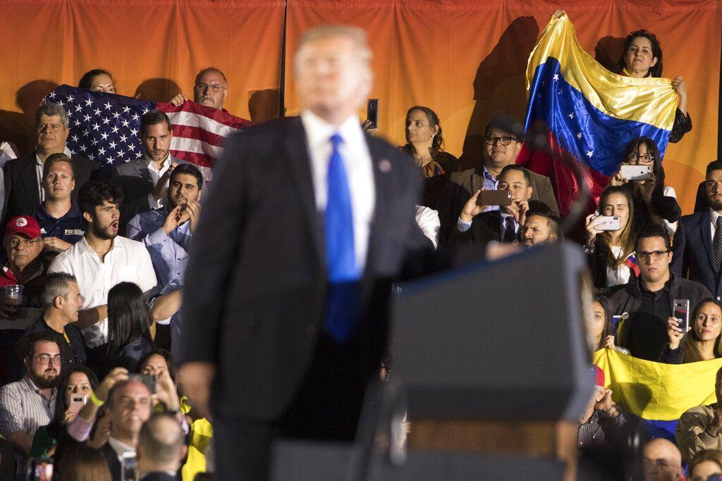 Personas de la audiencia ondean banderas de Venezuela y de Estados Unidos mientras el presidente Donald Trump habla ante la comunidad venezolana-estadounidense en el Centro Florida Ocean Bank Convocation de la Universidad Internacional de Florida el lunes 18 de febrero de 2019, en Miami. (AP Foto/Andrew Harnik)