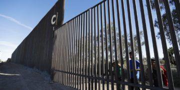 Niños en una sección de la vieja estructura fronteriza desde Mexicali, México, junto a una sección más alta y nueva en Calexico, California. Foto: Gregory Bull / AP / Archivo.