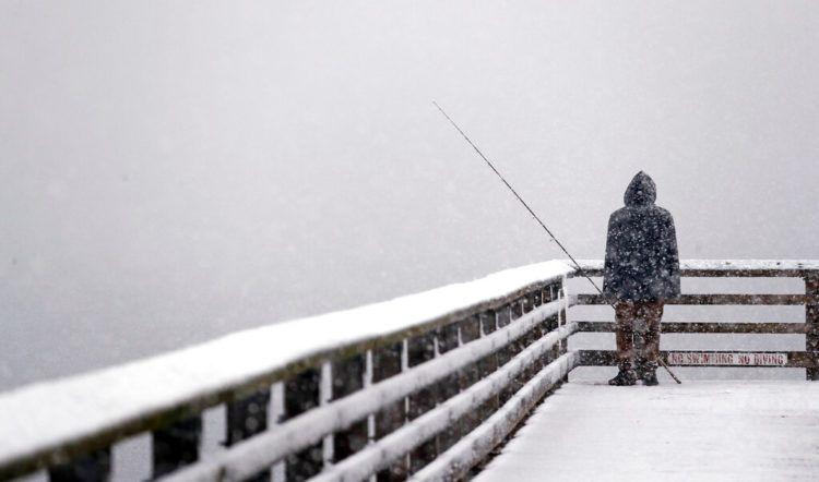 Hershel Odle mira al horizonte, completamente blanco por una tormenta de nieve, mientras pesca en un muelle el viernes 8 de febrero del 2019, en Seattle. Foto: Elaine Thompson / AP.