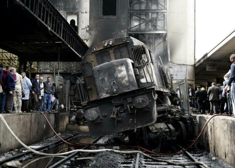 Personas observan un tren dañado tras una colisión y un posterior incendio en el interior de la estación de tren de Ramsés, en El Cairo, Egipto, el 27 de febrero de 2019. Foto: Nariman El-Mofty / AP.
