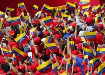 Seguidores del presidente Nicolás Maduro ondean banderas de Venezuela durante un acto en Caracas, Venezuela, el 2 de febrero de 2019. Foto: Ariana Cubillos / AP.