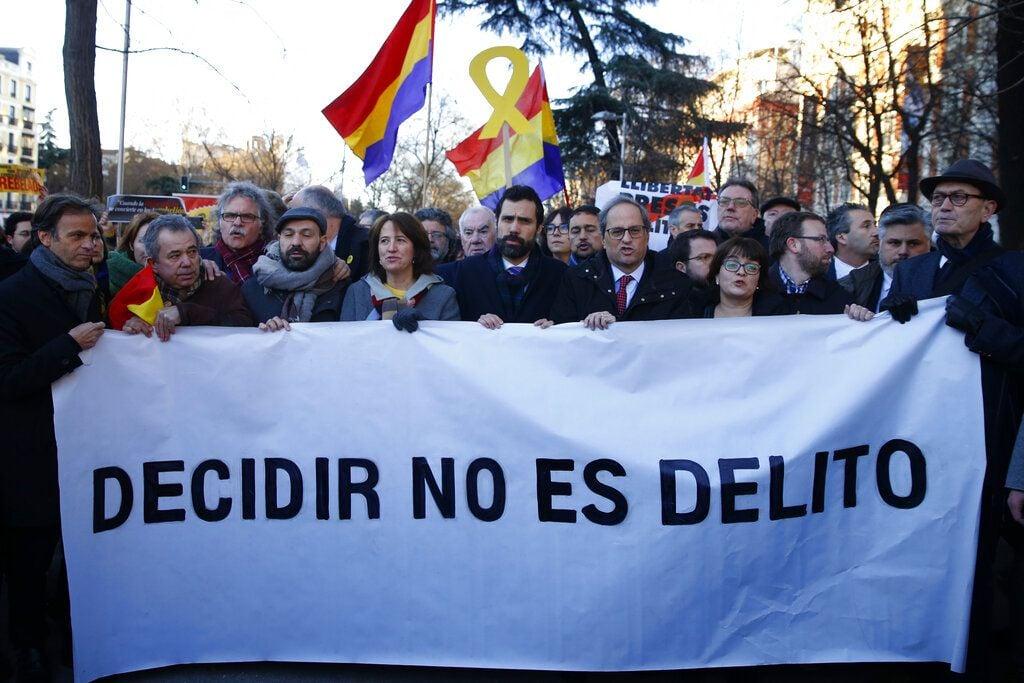 """El presidente del Parlamento de Cataluña, Roger Torrent (centro), y el del gobierno regional, Quim Torra (centro derecha), posan con un cartel con el lema """"Decidir no es delito"""", en el exterior del Tribunal Supremo, en Madrid, el 12 de febrero de 2019, en el inicio del juicio contra líderes independentistas. Foto: Andrea Comas / AP."""
