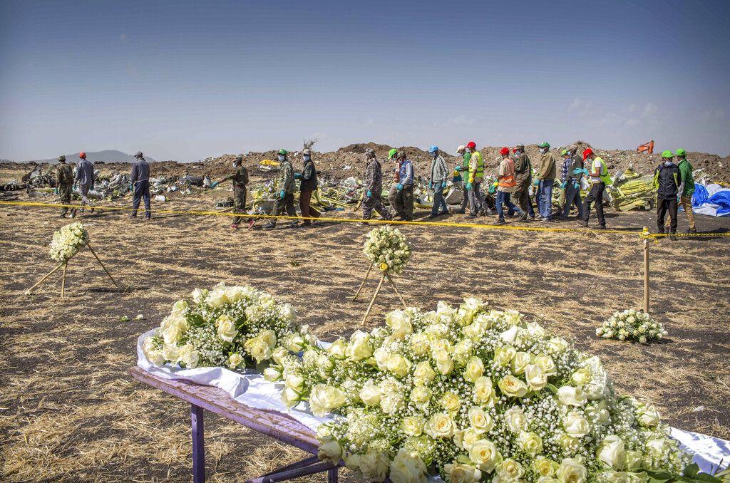 Un grupo de operarios pasa junto a las flores depositadas en el lugar donde se estrelló un Boeing 737 Max 8 de Ethiopian Airlines poco después de despegar con 157 personas a bordo, cerca de Bishoftu, o Debre Zeit, al sur de Adís Abeba, en Etiopía, el 13 de marzo de 2019. Foto: Mulugeta Ayene / AP.