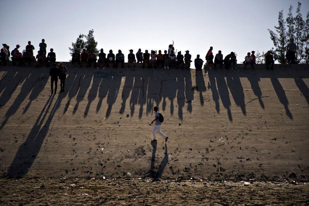 Migrantes cerca del paso fronterizo del Chaparral observan los enfrentamientos con la patrulla fronteriza de Estados Unidos, vistos desde Tijuana, México. (AP Foto/Ramón Espinosa, archivo)