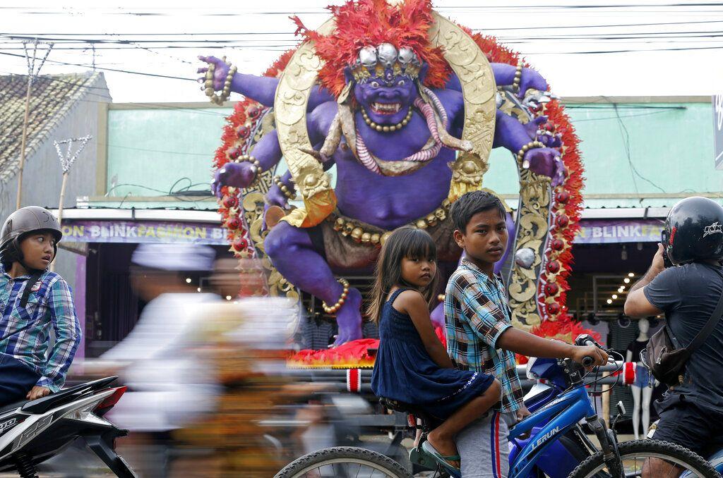 """Dos niños en bicicleta pasan por delante de una escultura gigante conocida como """"ogoh-ogoh"""", que representa a los espíritus malvados para celebrar el Nyepi, el día anual del silencio que celebra el inicio del año nuevo hindú balinés, en Bali, Indonesia, el 6 de marzo de 2019. Foto: Firdia Lisnawati / AP."""