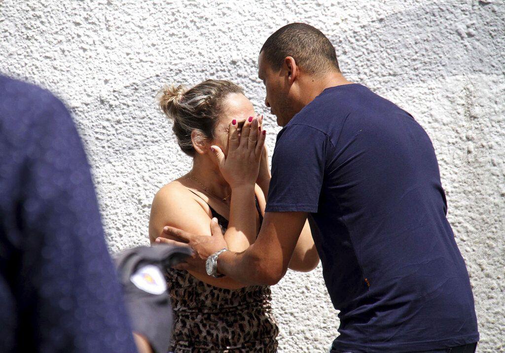 Un hombre conforta a una mujer en las afueras de la Escuela Estatal Raul Brasil en Suzano, Brasil, el miércoles, 13 de marzo del 2019. Dos adolescentes con capuchas abrieron fuego en una escuela pública el miércoles en el sur de Brasil, matando a seis personas antes de suicidarse, dijeron las autoridades. (Mauricio Sumiya/Futura Press via AP)