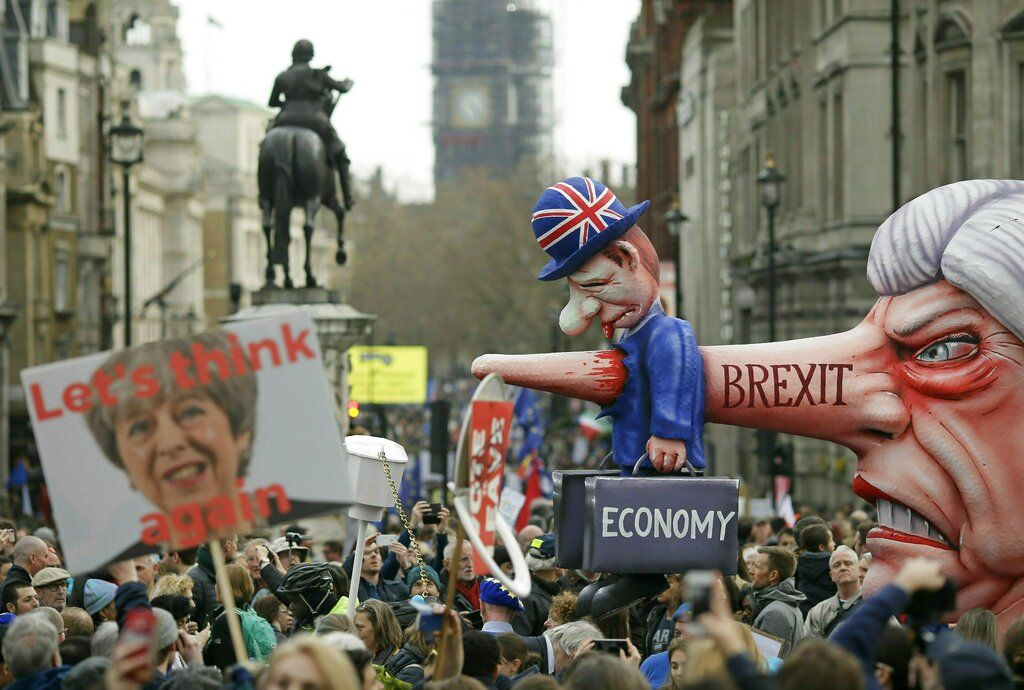Marcha anti-Brexit en la Plaza Trafalgar, en Londres, el sábado 23 de marzo del 2019. A la derecha se ve un muñeco gigante con el rostro de la primera ministro británica Theresa May, que también aparece en un cartel a la izquierda.  (AP Foto/Tim Ireland)