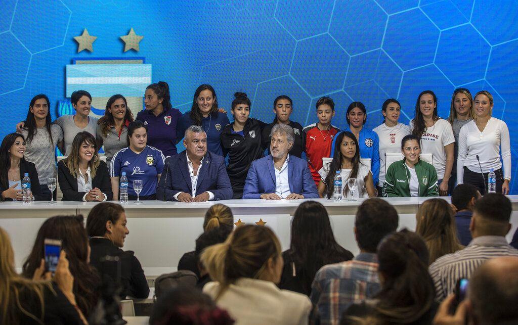 Acompañado por futbolistas, Claudio Tapia (centro), presidente de la Asociación del Fútbol Argentino, y Sergio Marchi, secretario general de la Unión de Futbolistas de Argentina, durante una rueda de prensa en la que se anunció la profesionalización de la liga femenina de fútbol. (AP Foto/Daniel Jayo)