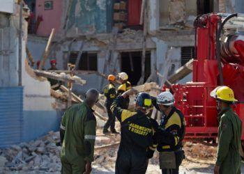 Miembros de una brigada de Rescate y Salvamento trabajan entre los escombros de un edificio que se derrumbó y causó la muerte de un hombre este jueves, en la esquina de Calzada del Cerro y Avenida Boyeros en La Habana, según fuentes oficiales. Foto: Yander Zamora / EFE.
