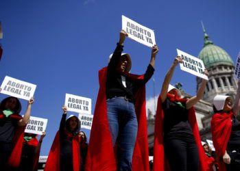 """Activistas por el aborto libre vestidas como personajes de la novela convertida en serie de televisión """"El cuento de la criada"""", sostienen pancartas en el Día Internacional de la Mujer en Buenos Aires, Argentina, el viernes 8 de marzo de 2018. Foto: Natacha Pisarenko / AP."""