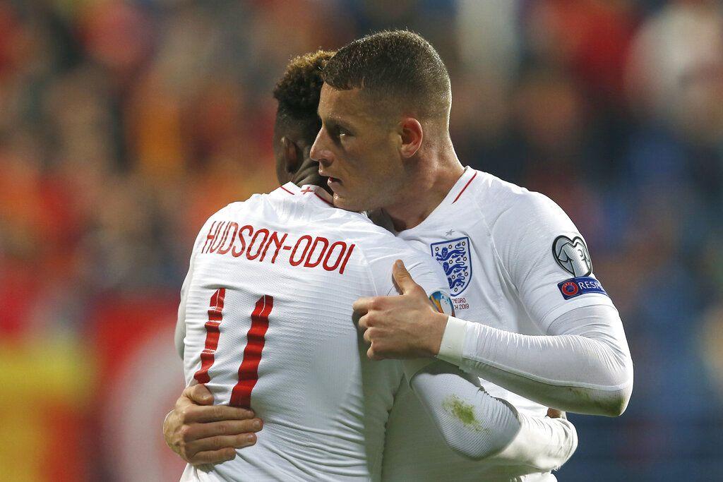 Callum Hudson-Odoi abraza a Ross Barkley, para felicitarlo por un gol con Inglaterra ante Montenegro, en un cotejo de la eliminatoria hacia la Euro, el lunes 25 de marzo de 2019, en Podgorica. Foto: Darko Vojinovic / AP.