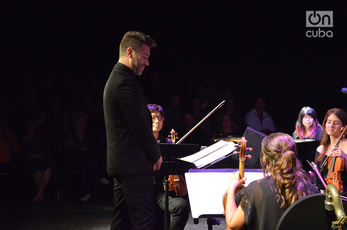 """Jacomo Bairos, director artístico y co-fundador de la orquesta Nu Deco Ensemble escucha un """"solo"""" de Yusa durante el concierto. Foto: Marita Pérez Díaz."""