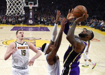 LeBron James, de los Lakers de Los Ángeles (derecha), lanza a canasta ante sus rivales de los Nuggets de Denver Torrey Craig (centro) y Nikola Jokic, durante la primera mitad del juego de la NBA que enfrentó a ambos equipos, el 6 de marzo de 2019, en Los Ángeles. (AP Foto/Mark J. Terrill)