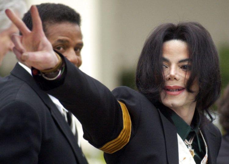 En esta foto del 2 de marzo del 2005, Michael Jackson saluda a sus fans al llegar a su juicio por abuso de menores en la Corte Superior del Condado de Santa Bárbara en Santa María, California. Foto: Michael A. Mariant / AP.