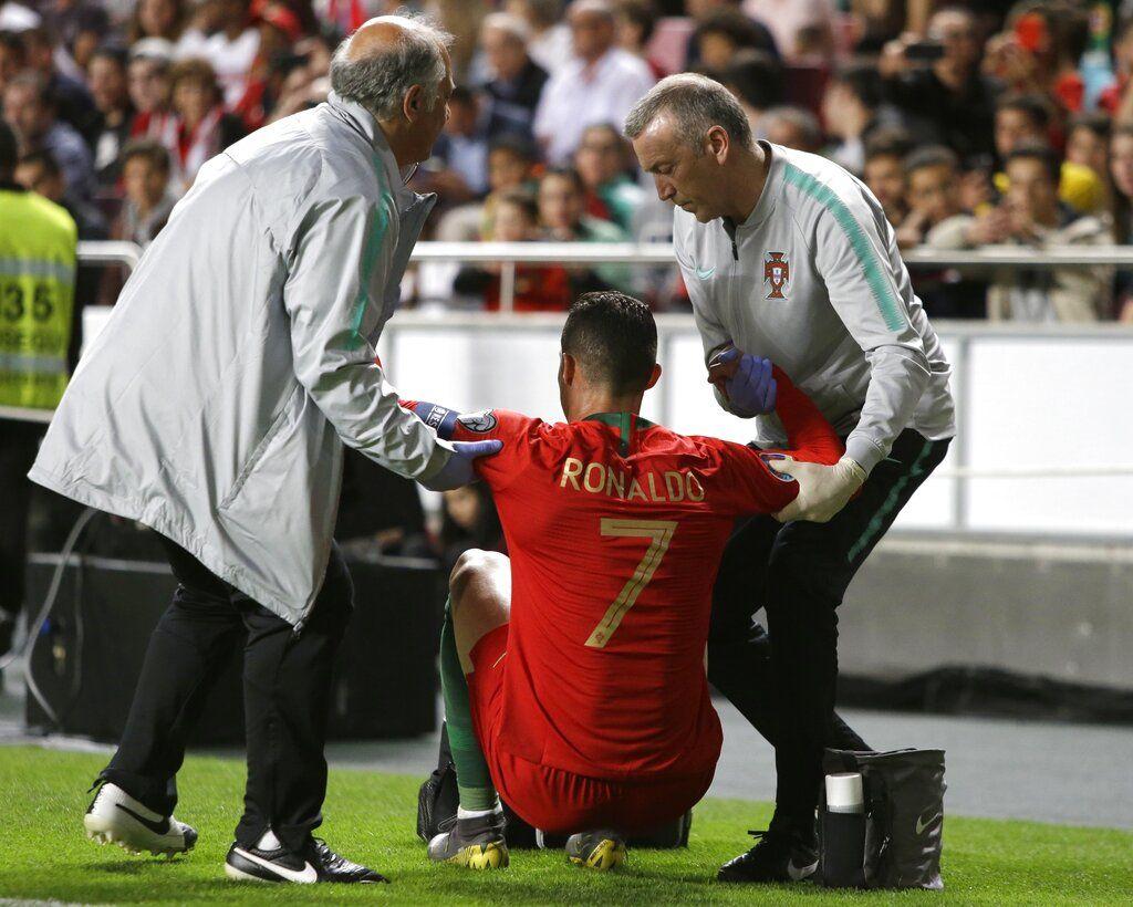 Tras sufrir una lesión, el portugués Cristiano Ronaldo recibe ayuda del cuerpo médico durante un encuentro de la eliminatoria rumbo a la Eruocopa, el lunes 25 de marzo de 2019, ante Serbia, en Lisboa. Foto: Armando Franca / AP.