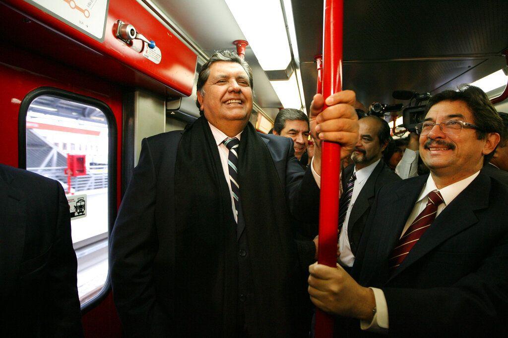 En esta foto de archivo del 11 de julio de 2011 el entonces presidente saliente de Perú, Alan García, a la izquierda, viaja en el sistema de tren eléctrico en Lima, Perú. (AP Foto / Martín Mejía, Archivo)